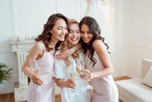 Bride With Bridesmaids Embraci...