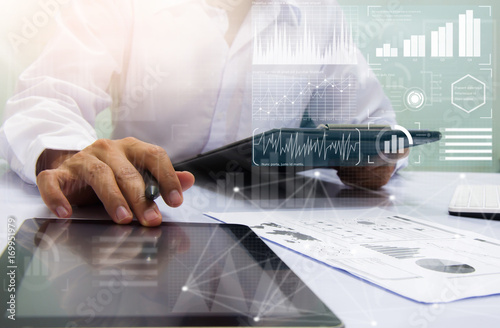 Fototapeta businessman working with business documents on office table with digital tablet computer and graph finance diagram in the background obraz na płótnie