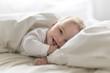 Leinwandbild Motiv Cute happy 7 month baby girl in diaper lying and playing
