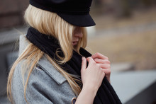 Wrap Up In A Warm Scarf. Stylish Young Blonde In A Black Cap And Scarf