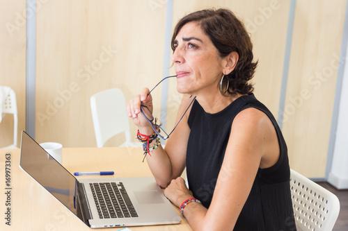 Fényképezés Mujer sentada frente al ordenador reflexionando con la mirada en el infinito