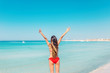 From behind: happy young woman on a paradisiac beach