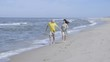 Happy lovely couple running along the seacoast barefoot and enjoys herself. Beach with white sand. Outgoing coastal line. Slow Motion.