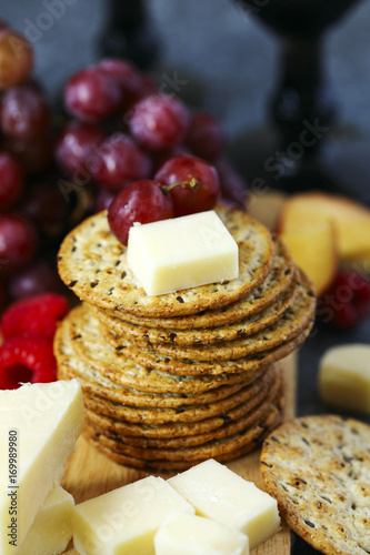 Valokuva  Cheddar cheese, crackers and fruits on wooden board