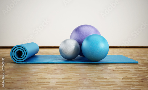 Photo  Pilates mat and exercise balls standing on parquet floor
