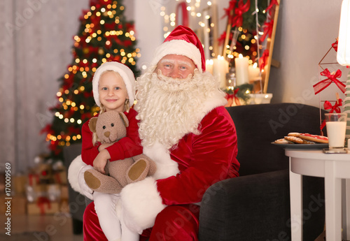 d83e053d9 Santa Claus and cute little girl with toy in room decorated for Christmas