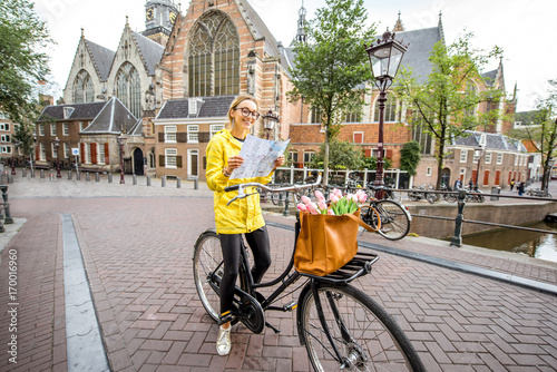 Photo  Portrait of a woman tourist in yellow raincoat standing with map and bicycle wit