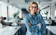 Happy Female Designer Standing In Office