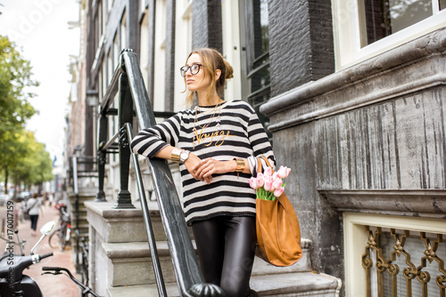Photo  Portrait of a young and elegant woman standing with bag and flowers on the stair