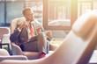 Leinwanddruck Bild - Positive businessman sitting in the departure lounge