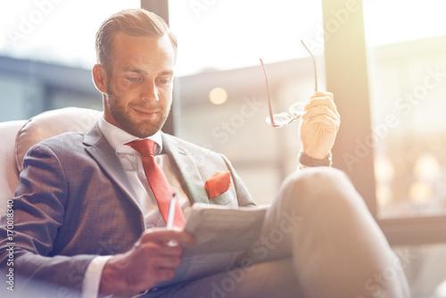 Positive handsome businessman reading a newspaper Canvas Print