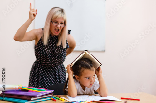 the teacher screams at the little schoolgirl Wallpaper Mural