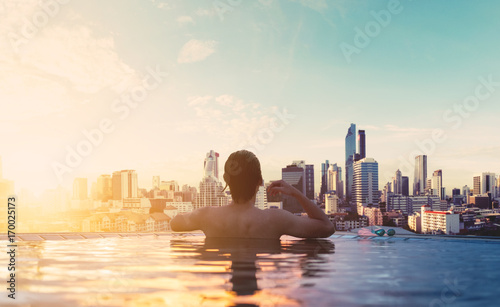 a man relax in swimming pool in sunrise, on rooftop in the city
