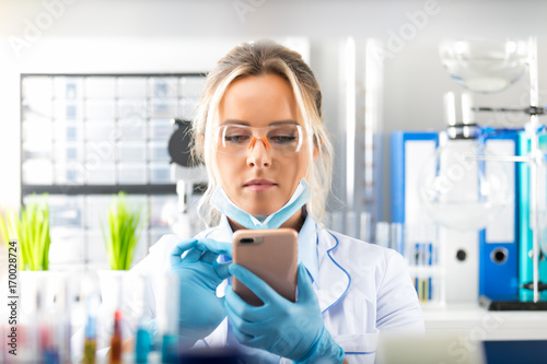 Photographie Young attractive woman scientist using smartphone in the laboratory