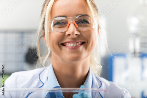 Fotografia  Happy young attractive smiling woman scientist in the laboratory