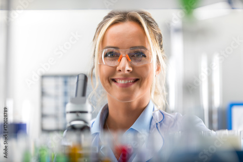 Canvastavla Happy young attractive smiling woman scientist in the laboratory