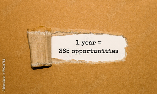 Fényképezés  The text 1 year is 365 opportunities appearing behind torn brown paper