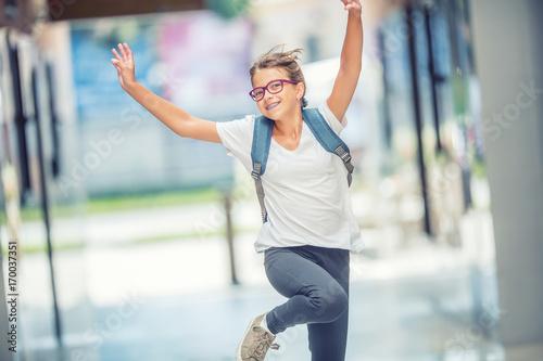 Plakat Uczennica z torbą, plecakiem. Portret nowożytna szczęśliwa nastoletnia szkolna dziewczyna z torba plecakiem. Dziewczyna z aparatami ortodontycznymi i okulary