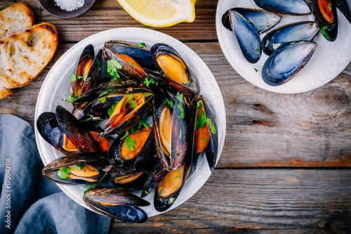 Foto op Plexiglas Schaaldieren Delicious seafood mussels with with sauce and parsley. Lemon and baguette . Clams in the shells.