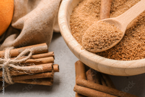 Canvas Prints Condiments Cinnamon sticks and sugar in wooden bowl with spoon on grey background, closeup