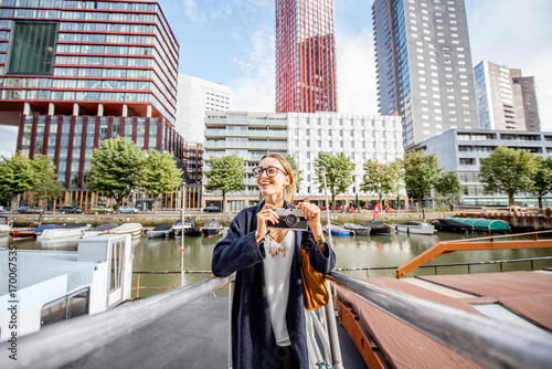 Foto op Canvas Rotterdam Young woman traveling at the modern harbor with skyscrapers on the background in Rotterdam city