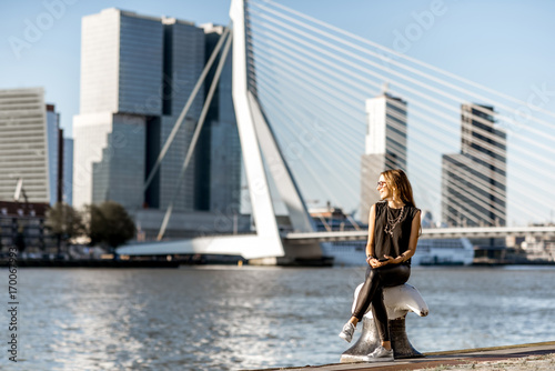 Foto op Canvas Rotterdam Woman enjoying beautiful cityscape view on the modern riverside during the morning in Rotterdam city