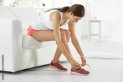 Fotografía  Young sporty woman tying shoelaces at home