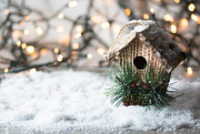 Beautiful Christmas Composition With Birdhouse. Wooden Grey,snow Background.Place For Text. Garland Light,bokeh Effect.