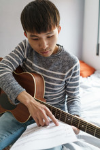 Young Chinese Man With Guitar Pointing On The Music Sheet