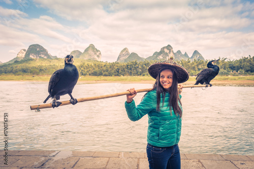 Valokuva  Portrait of beautiful girl  with two cormorants nearby Li river, Yangshuo, Chuin