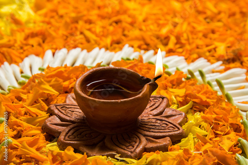 Flower Rangoli For Diwali Or Pongal Or Onam Made Using Marigold Or Zendu Flowers And Red Rose Petals Over White Background With Diwali Diya In The Middle Selective Focus Buy This