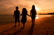 Silhouette of little kid girls enjoy on the beach with sea and sunset background