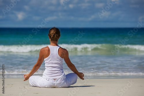 Stampe Caucasian woman practicing yoga at seashore of tropic ocean