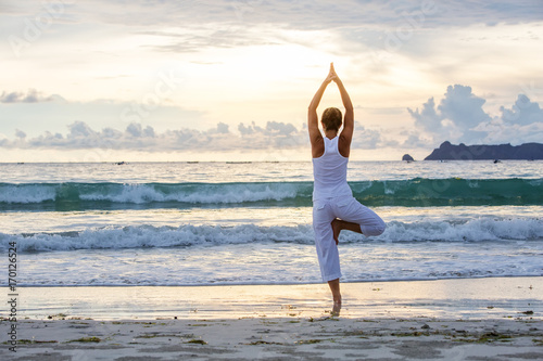 Stampa su Tela Caucasian woman practicing yoga at seashore of tropic ocean