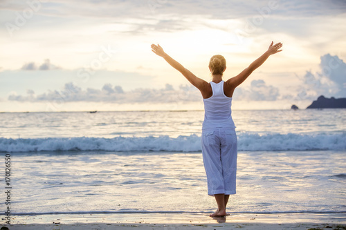 Valokuva  Caucasian woman practicing yoga at seashore of tropic ocean