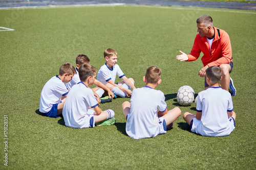 mata magnetyczna Portrait of boys team sitting in front of coach on football field listening to pre game speech