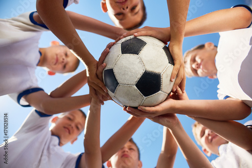 fototapeta na ścianę Low angle view of boys in junior football team standing in circle holding ball together against blue sky, focus on ball