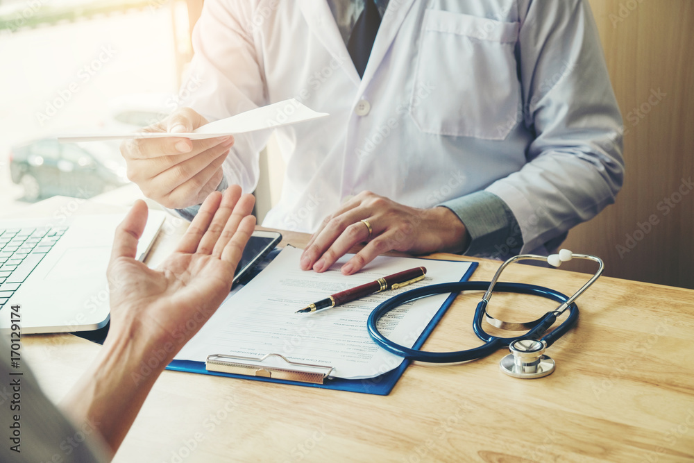 Fototapeta Doctor or physician writing diagnosis and giving a medical prescription to female Patient