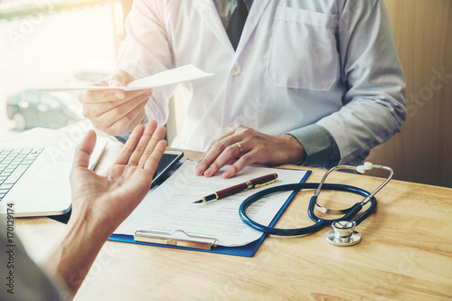 Fotografia  Doctor or physician writing diagnosis and giving a medical prescription to femal