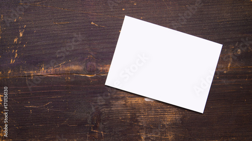 Fotomural a white blank postcard template for graphic design on a wooden background