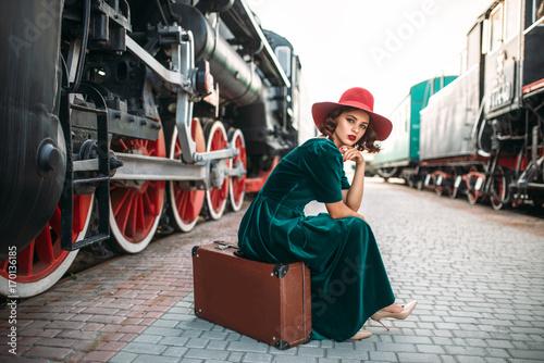 Fotografía Woman in red hat against vintage steam train