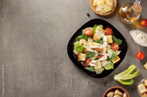 Fotografía  caesar salad and ingredients at table