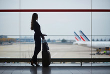 Woman In The Airport, Looking Through The Window At Planes