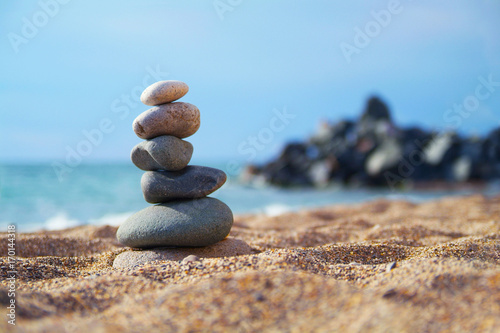 Photo sur Plexiglas Zen pierres a sable Stones laid out in the form of a pyramid on the seashore