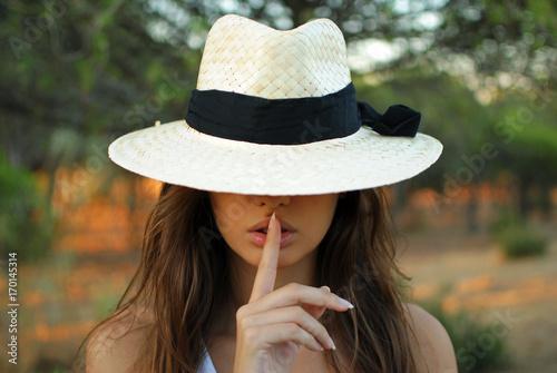 Fotografie, Obraz  chica joven con sobrero y con un dedo en sus labios indicando silencio