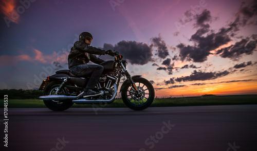 Fototapeta Mężczyzna jedzie sportster motocykl podczas zmierzchu.