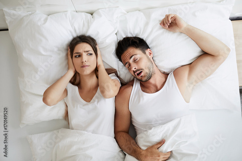 Photo Stressed young woman covering her ears because her husband is snoring