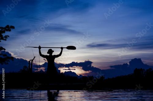 Plakat Sylwetka rybak pozycja na łodzi, chwyta paddle, na zmierzchu tle.