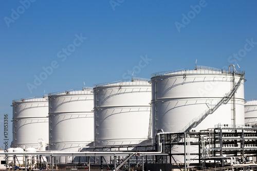 Fényképezés  Row of large white oil storage tank silo's