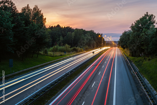 Speed traffic on highway at dusk. Colorful light trails on the street. Poland.